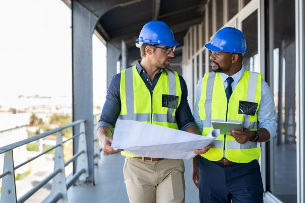architects-discussing-plan-at-construction-site-SJWQB73